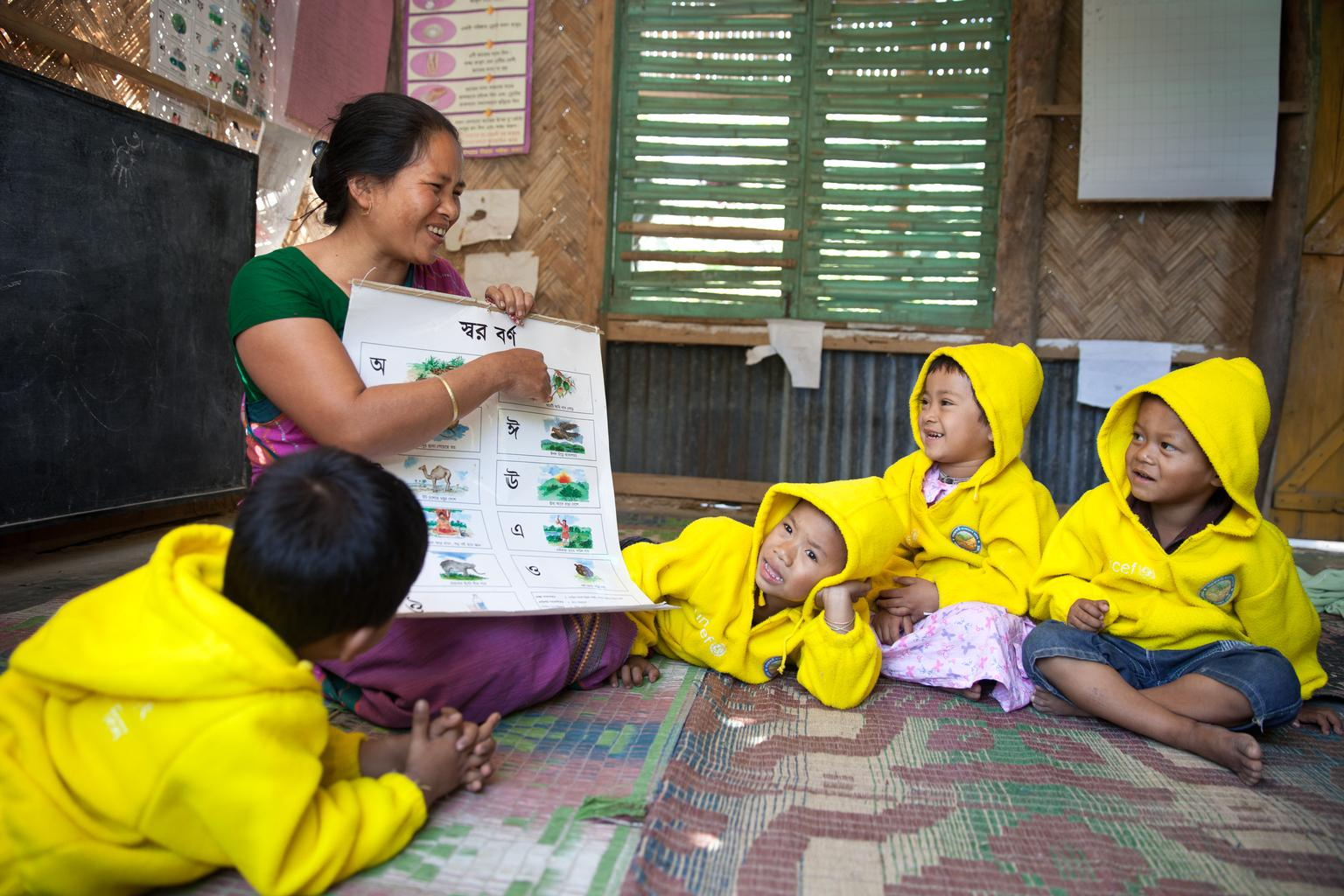 Shwapna Devi Chakma, a para worker helps a students learn alphabets at a pre-primary school in a para center in Rangamati on 2 February, 2014.